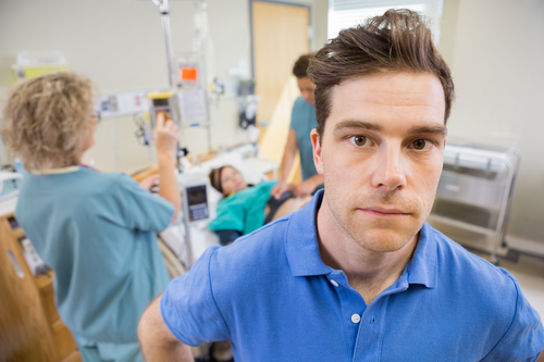 Worried Man With Nurses Examining Pregnant Woman In Hospital
